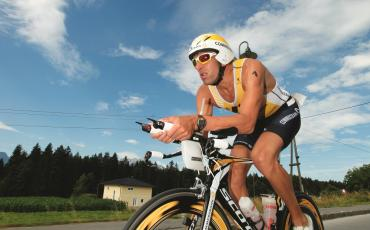 image of triathlete cycling in race